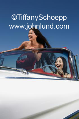Pic of a couple of women smiling and happy driving in a convertible car with the top down. The woman in the passenger position is standing up.